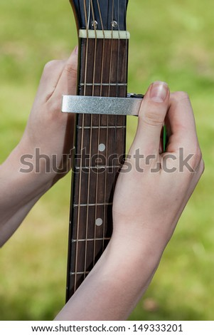 A man puting a capo on a guitar - stock photo