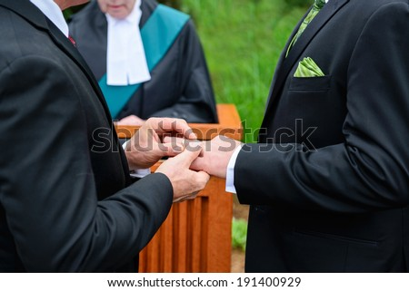 A man putting a ring on another man's finger during their wedding ceremony.  - stock photo