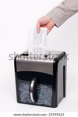A man putting confidential documents into a paper shredder - stock photo
