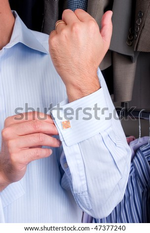 A man putting on his cuff links - stock photo