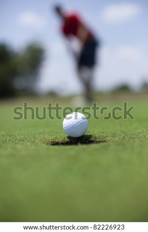 A man putts a golf ball on the green. - stock photo