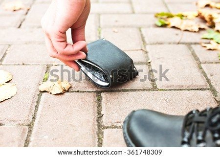 A man raises his black wallet with money on the street - stock photo