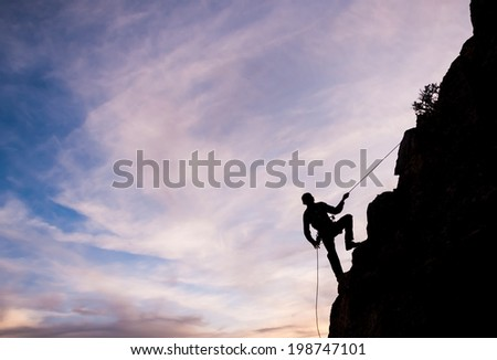 A man rappels down a mountain face during sunset