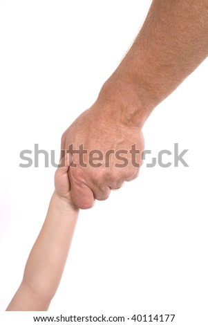 A man reaching out and grabbing a child's hand for support. - stock photo