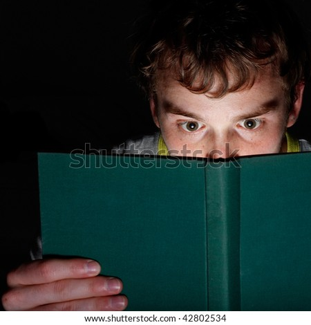 A man reading a book at night - stock photo