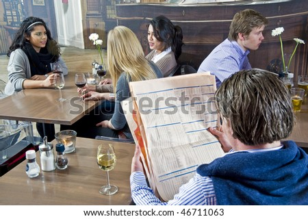 A man reading a financial paper with several people at different tables in the same cafe - stock photo