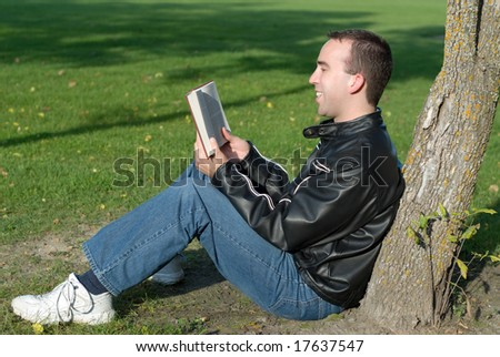 A man reading a humorous book outside - stock photo