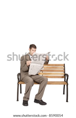 A man reading the classified ads on a park bench, on a white background. - stock photo