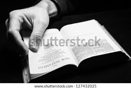 A man reading the Holy Bible with one hand. - stock photo