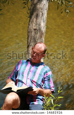 a man reads a book outside - stock photo