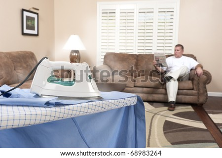 A man reads his newspaper and forgets about the steaming hot iron that is scorching his dress shirt. - stock photo