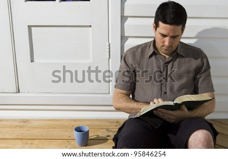 A man reads the Bible sitting on the back step