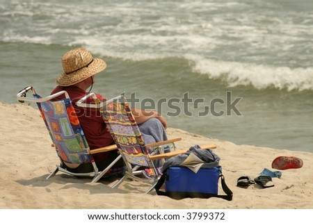 A man relaxes on the beach alone, watching the waves. Fort Fisher, North Carolina. - stock photo