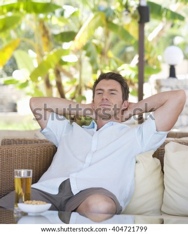 A man relaxing with a drink - stock photo