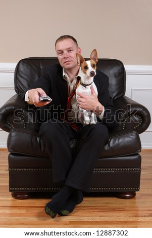 A man relaxing with his dog and his remote control after a long day at work. - stock photo