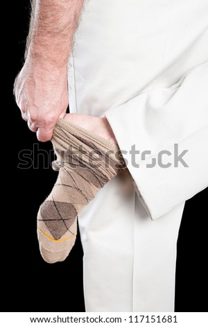A man removing his socks shows several inferences regarding dexterity and daily tasks adults conduct. - stock photo