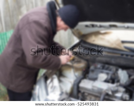 a man repairs the car creative abstract blur background with bokeh effect
