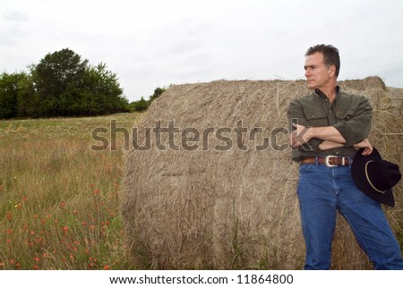 A man resting against a large round bale of hay. - stock photo