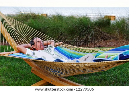 A man rests near the beach in a hammock.