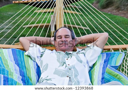 A man rests near the beach in a hammock. - stock photo