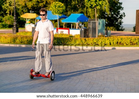 A man rides a hoverboard giroskutere or on a sunny day in the park