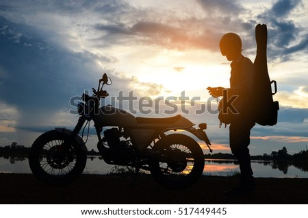 A man riding motorcycle,Silhouettes picture ,play guitar