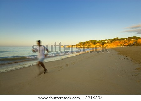 a man running at the beach in the morning - stock photo