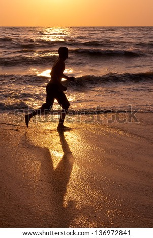 a man running for fitness and wait loss by the sea in summer evening with big shadow of man on beach. jog workout in beach at dawn Kovalam beach Kerala India sunset background. Unplugged  - stock photo
