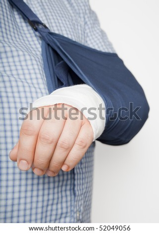 A man's arm in bandages and a sling after surgery. His fingers are stained orange from surgical antiseptic. - stock photo