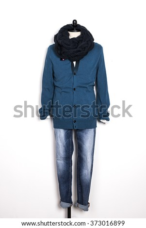 A man's blue cardigan with muffler and blue denim(jeans, trousers) with mannequin on the wall isolated white.  - stock photo