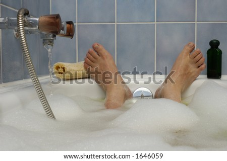 A man's feet, poking out of a bubble bath, with water running in to the side. A loofah and bottle of bath lotion to either side. Space for text on the blue tiled wall above the feet. - stock photo