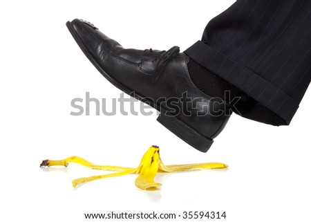 A man's foot about to slip on a banan peel, Danger or accident concept. - stock photo