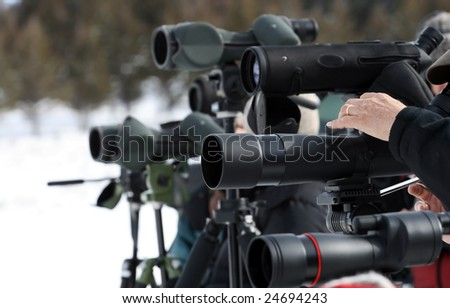 A man's hand adjusts his telescope which is among many other scopes. - stock photo