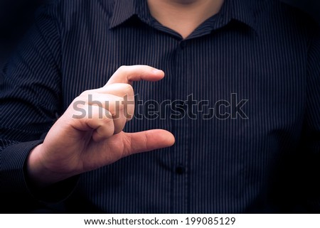 A man's hand holding a gadget or showing size of something - stock photo