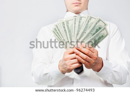 A man's hand holding a handful of dollars. - stock photo