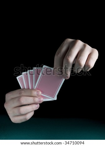 A man's hand holding five cards over a green felt. - stock photo