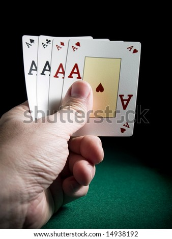A man's hand holding four aces over a green felt.
