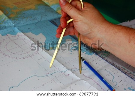 A Man's Hand Plotting a Route on a Maritime Chart - stock photo