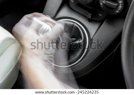 A man's hand shifting a car gearbox - stock photo