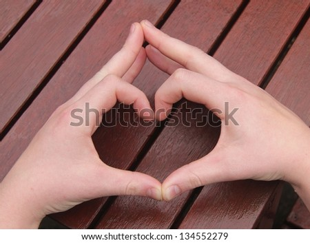 A man's hands make heart sign on wooden background - stock photo