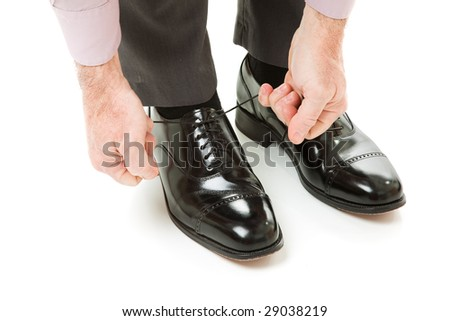 A man's hands tying the laces on a new pair of dress shoes.  Isolated on white.