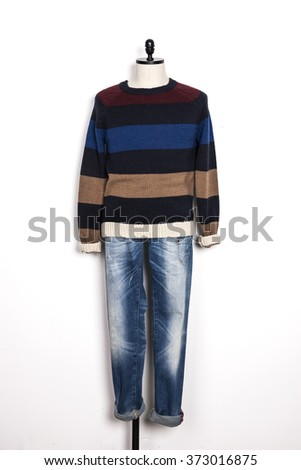 A man's military blue, brown, black sweater and blue denim(jeans, trousers) with mannequin on the wall isolated white.  - stock photo