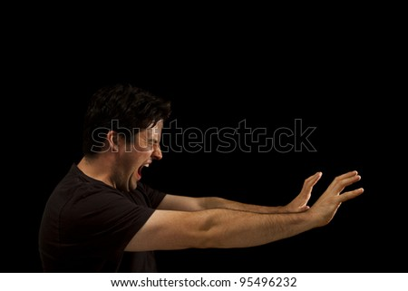 A man screams out and reaches forward. Isolated on black - stock photo