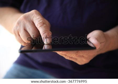 A man searches the internet on his tablet. - stock photo