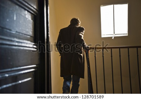 A man seen from behind is going down the staircase in an old parisian building. - stock photo
