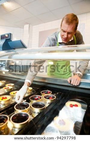 A man selling gourmet deserts from behind a glass counter - stock photo