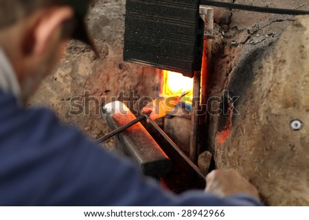 a man shaping a glass bead like a fish - stock photo