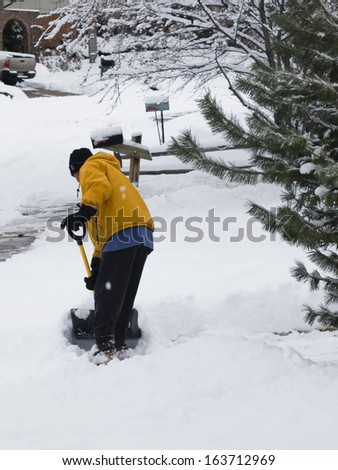 A man shoceling his sidewalk. - stock photo