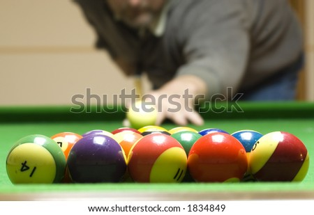 A man shooting a game of pool - stock photo