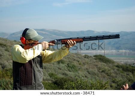 A man shooting a shotgun on the trap range  - stock photo